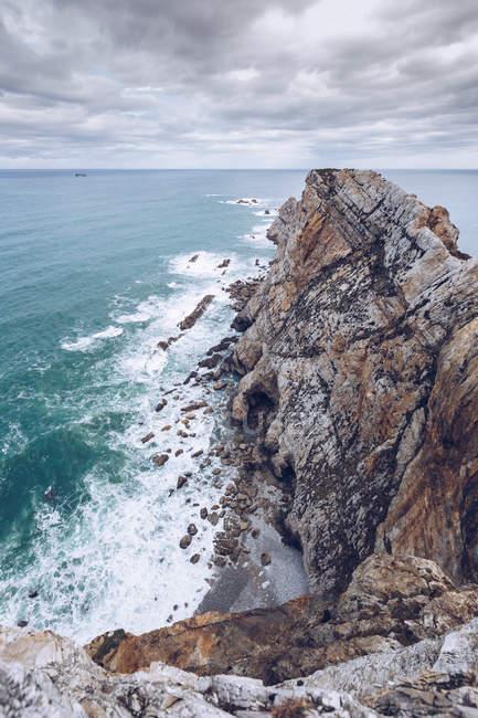 Increíble vista del agua de mar salpicando cerca de un largo acantilado rocoso en un día nublado en Asturias, España - foto de stock