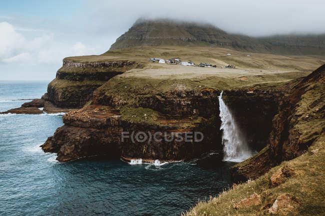 Falaises rocheuses vertes et cascade de pulvérisation sur les îles Feroe — Photo de stock