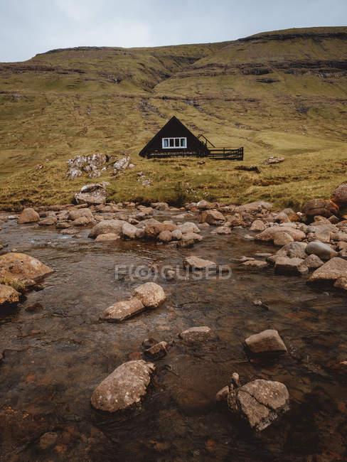 Одинокий традиционный сельский дом на плато на озере на Фарерские острова — стоковое фото