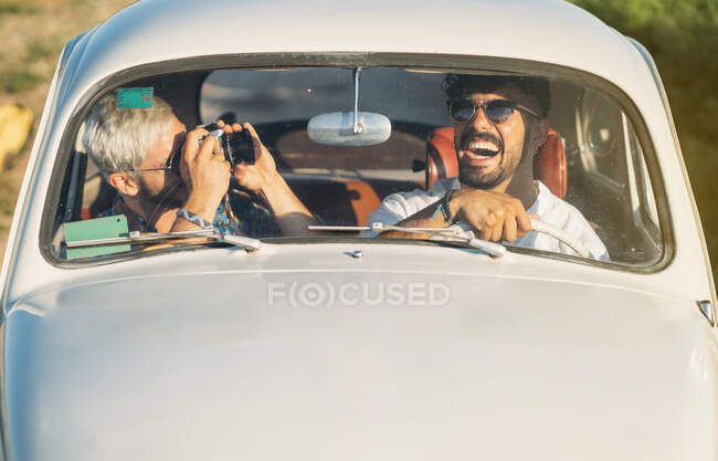 Two cheerful young guys with camera driving retro car and making pictures while travelling in countryside together — Stock Photo