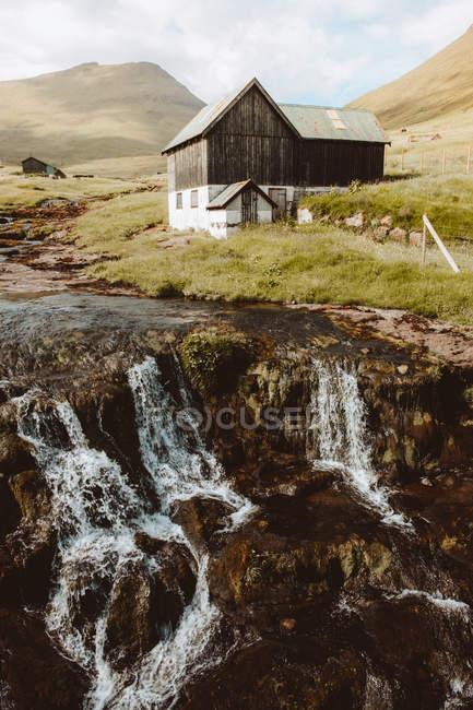 Cascata e casa rurale in legno su collina sulle isole Feroe — Foto stock