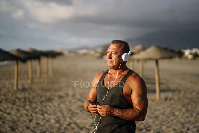 Літній чоловік слухає музику на пляжі. — стокове фото