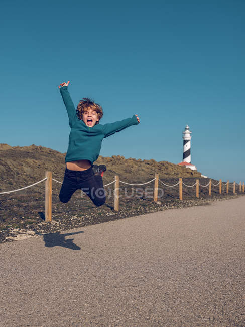 Cheerful cute boy having fun and jumping on background of beacon tower. — Stock Photo