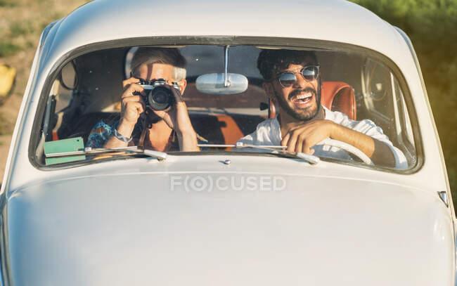 Due ragazzi allegri con macchina fotografica guida auto retrò e fare foto durante il viaggio in campagna insieme — Foto stock