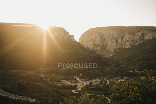 Breathtaking view of bright sun shining over beautiful mountains and picturesque valley — стокове фото
