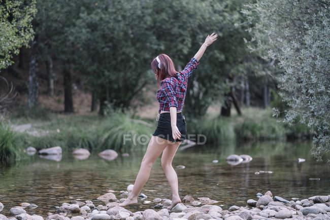 Chica pelirroja realiza ejercicios junto al río - foto de stock