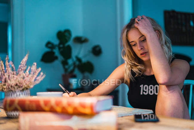 Blond woman sitting at table and planning journey with books and map — Stock Photo