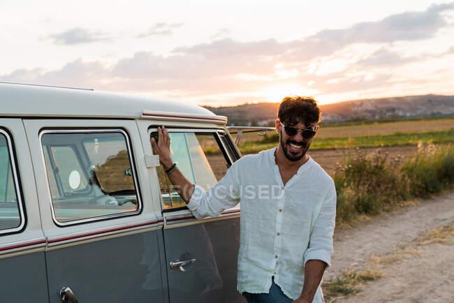 Привабливий молодий чоловік у стильному одязі весело посміхається і дивиться вгору, стоячи біля фургона ретро під час подорожі сільською місцевістю. — стокове фото