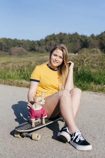 Девушка с собакой на длинном борту в природе — стоковое фото