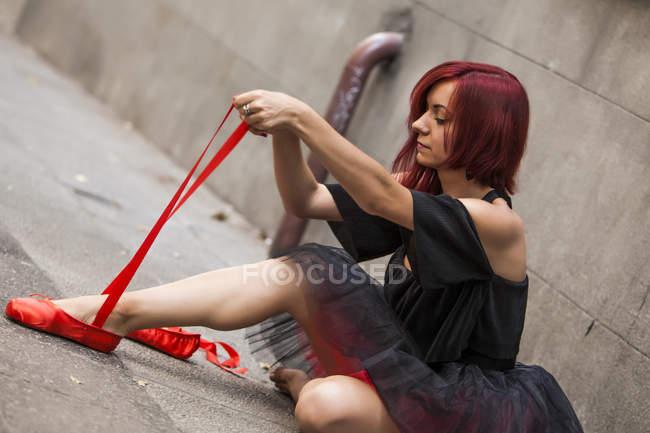 Tête de ballerine rouge avec tutu noir écrasant bouts de ballet rouge dans la rue — Photo de stock