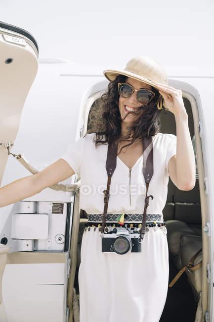 Sonriente mujer viajero con cámara de fotos saliendo del avión a su llegada al aeropuerto - foto de stock
