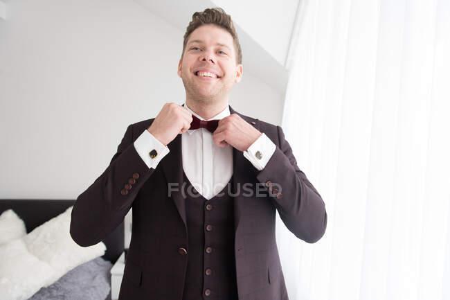 Jovem bonito sorrindo homem em traje preto de pé no quarto e colocando em gravata arco — Fotografia de Stock