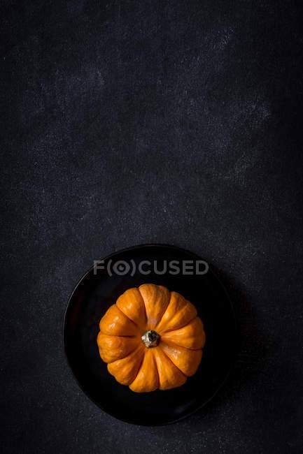 Decoración de Halloween de calabaza en placa sobre fondo oscuro con espacio de copia . - foto de stock