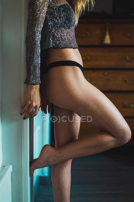 Nahaufnahme von unkenntlich schlanke sexuelle Frau in Schlüpfer und glitzernden Top stützte sich auf die Wand zu Hause — Stockfoto