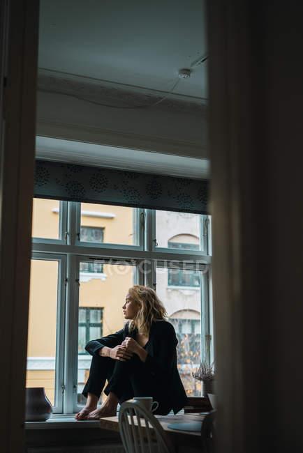 Романтический блондинка молодой женщины, сидя на подоконнике — стоковое фото