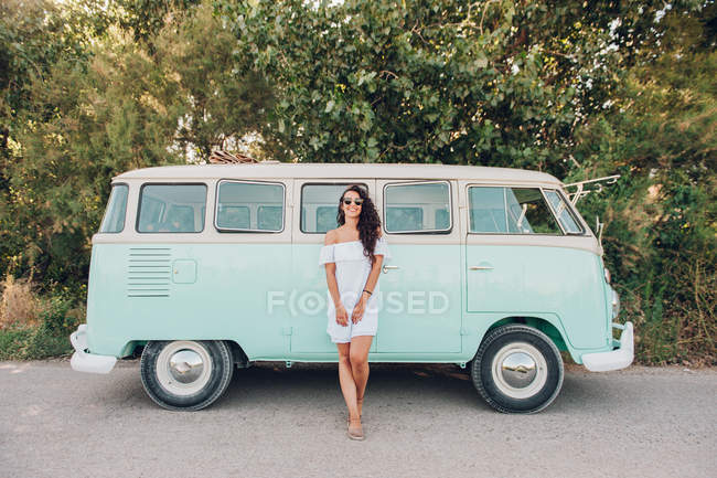 Cheerful brunette woman in sunglasses standing in front of van — Stock Photo