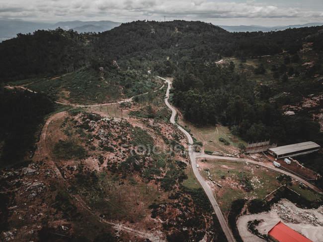Vue par drone d'une route de campagne étroite traversant une forêt sur un terrain vallonné incroyable pendant la journée nuageuse en Galice, Espagne — Photo de stock