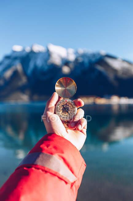 Людина, одягнена в червону куртку, тримає золотий компас в сонячний день на розмитому канадському тлі гір — стокове фото