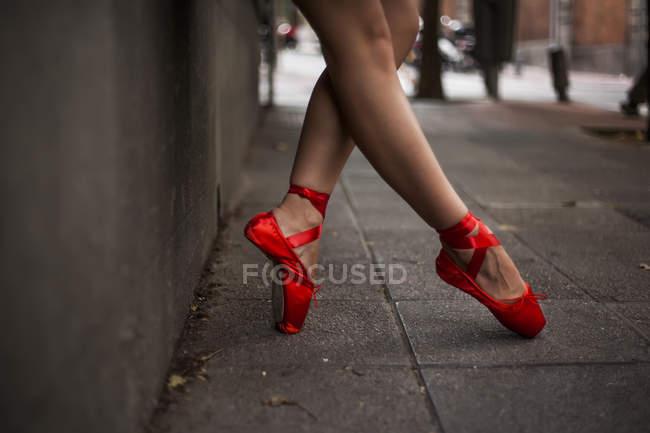 Обрезанное изображение балерины с красными балетными кончиками, согревающимися под танец на улице, исполняющими позы, закрытые под кончики балерины — стоковое фото