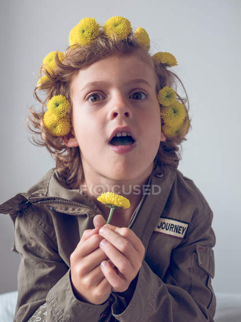 Мальчик с цветами в волосах, делая лица на сером фоне — стоковое фото