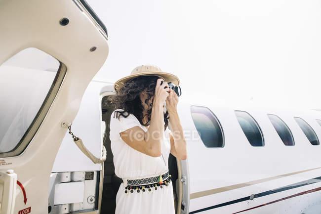 Em pé perto de avião e tirando foto de viagem — Fotografia de Stock