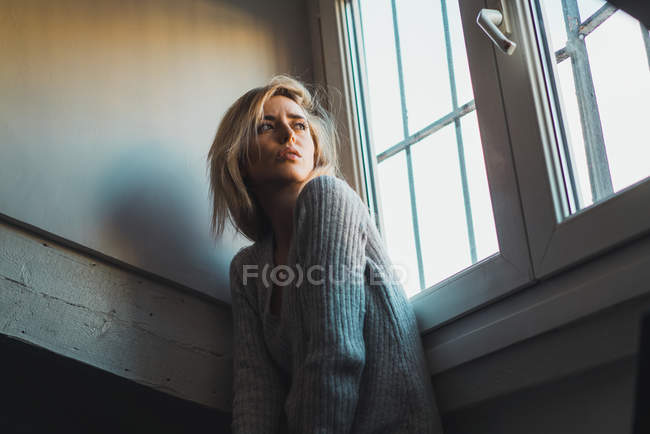 Pensive young blonde woman in sweater sitting at window and looking away — Stock Photo