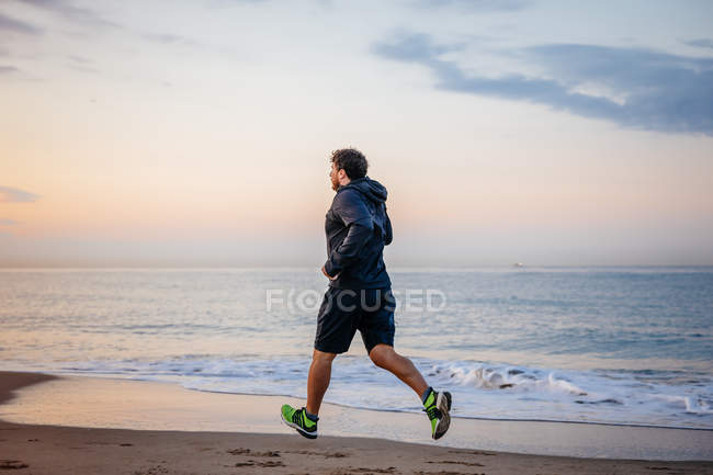 Man in sportswear running on sand at sea during outdoor workout on beach at sunset — Stock Photo
