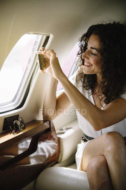 Portrait de prendre femme souriant à travers de la fenêtre de l'avion — Photo de stock