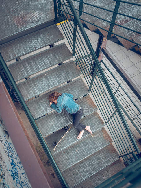 Sportive barefoot boy lying with skateboard on metal stairs — Stock Photo
