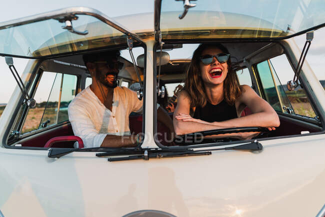 Cheerful man and woman smiling and sitting inside vintage van while traveling in countryside on sunny day together — Stock Photo