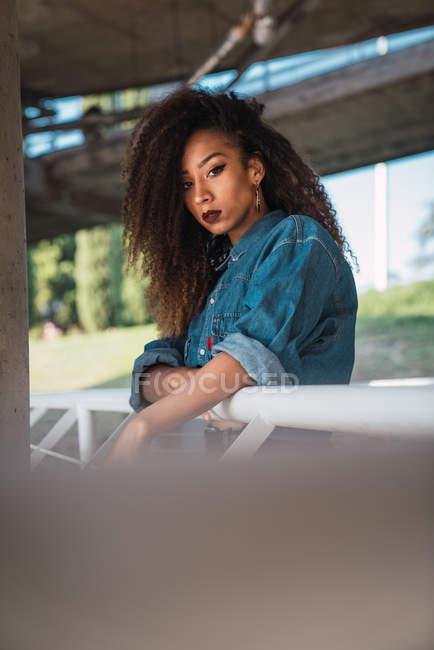 Giovane donna in camicia di jeans in piedi sul balcone vicino ringhiera e guardando la fotocamera — Foto stock