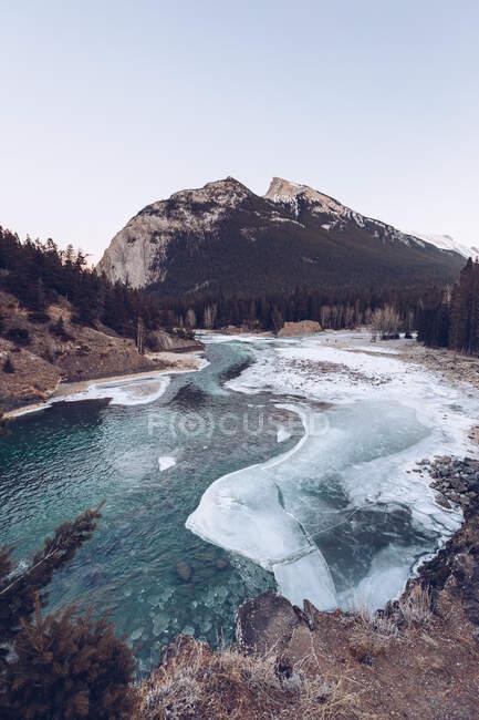 Río que corre en el lago derretido de las tierras altas en la hendidura nevada con rocas marrones y pocos abetos de invierno en el día soleado - foto de stock