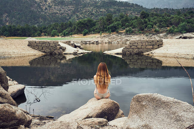 Back view of young woman with long hair in swimming suit sitting on big stone and looking at still lake on background on green trees and mountains — Stock Photo