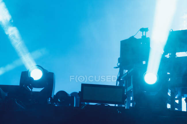 Blue spotlights illuminating stage and audience during amazing music show — Stock Photo