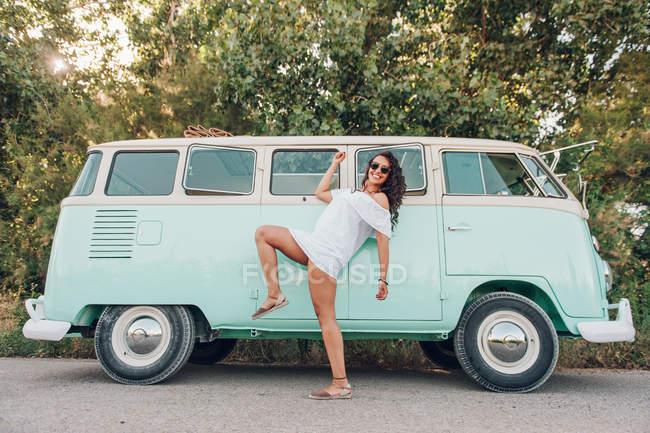 a25ab774bc5 Cheerful brunette woman in summer dress posing in front of bright van —  Stock Photo