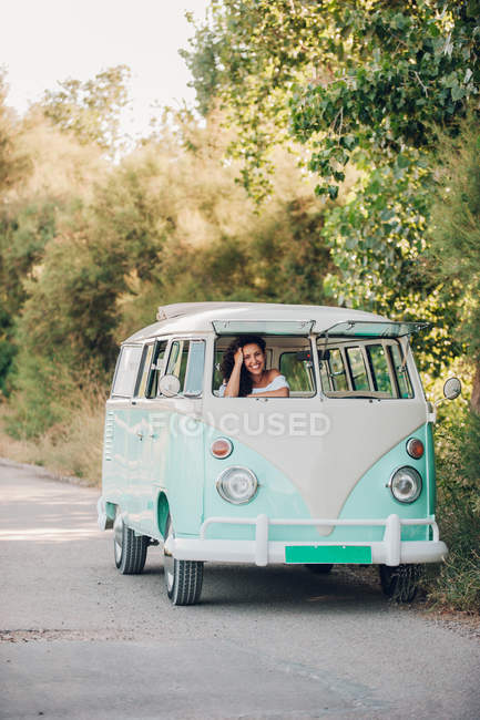 Smiling young woman sitting in retro van in nature — Stock Photo