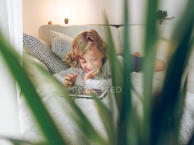 Сміючись хлопчик, використовуючи tablet на дивані в домашніх умовах — стокове фото