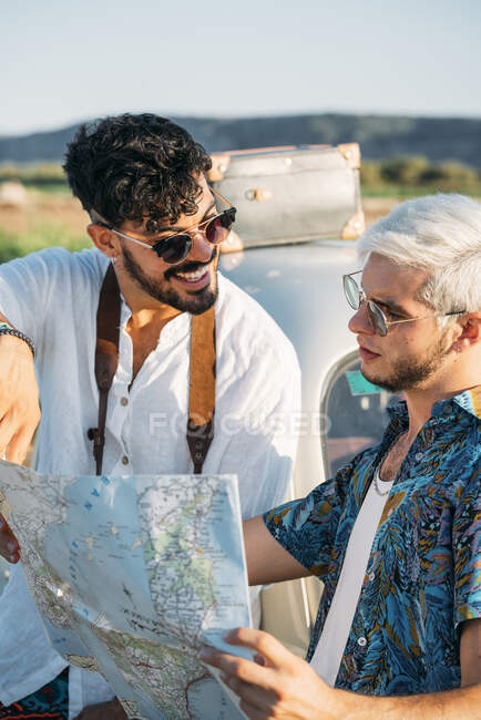 Two young guys with photo camera standing near retro car and looking at map while travelling in nature together — Stock Photo