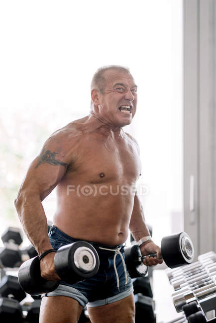 Muscular older man posing while training — Stock Photo