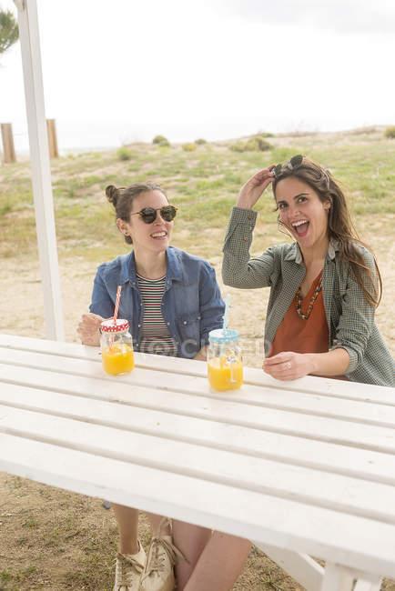 Mulheres sorridentes se divertindo com frascos com suco — Fotografia de Stock