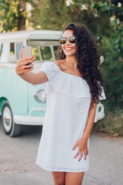 Joven alegre tomando selfie delante de la furgoneta en la naturaleza - foto de stock