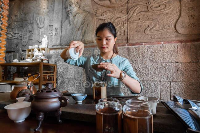 Jovem mulher asiática fazendo preparações e preparando chá oriental — Fotografia de Stock