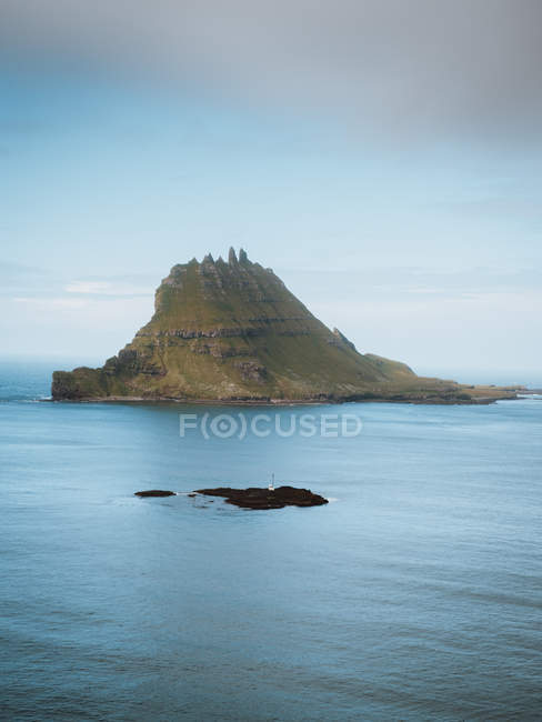 Picturesque view of calm blue ocean and rock on Feroe Islands — Stock Photo