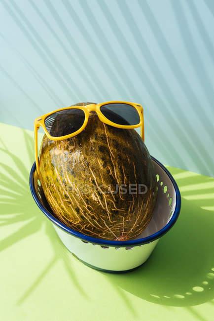 Свежей дыни с очками в чашу на синий и зеленый фон с тени пальмовых листьев — стоковое фото