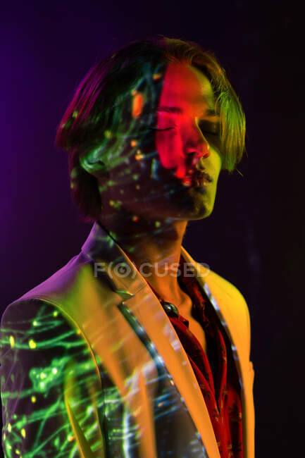 Attractive androgynous man keeping eyes closed while standing under colorful illumination in dark room — Stock Photo