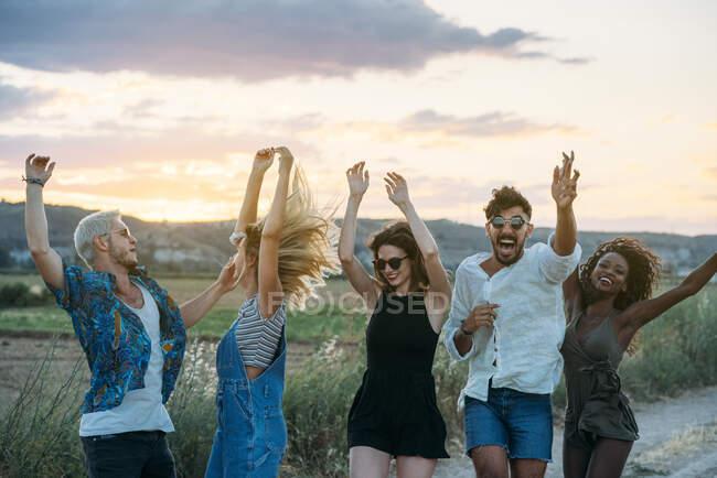 Gruppo di giovani in abiti casual ridere e ballare divertendosi nella splendida campagna insieme — Foto stock