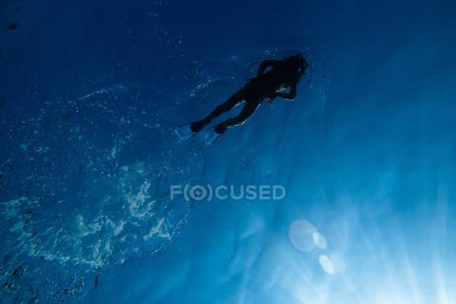 Снизу мнение до неузнаваемости человека в подводное снаряжение, купание в голубые воды моря — стоковое фото