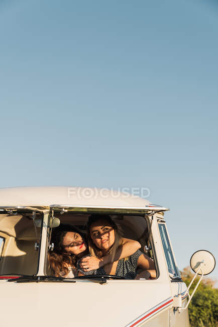 Two lovely women smiling and hugging while riding retro van during countryside trip on background of clear blue sky — Stock Photo