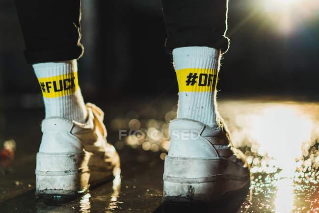 Ноги неузнаваемого человека в кроссовках с хештегами Fuck Off на носках ночью — стоковое фото