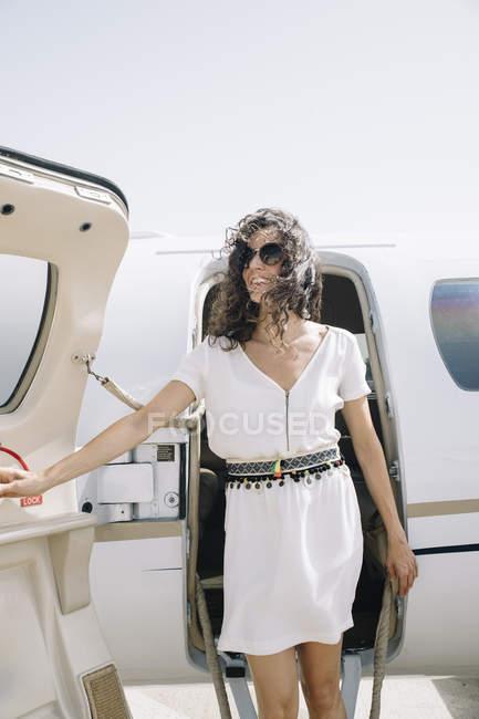 Viajero mujer sonriente saliendo de plano a la llegada al aeropuerto - foto de stock